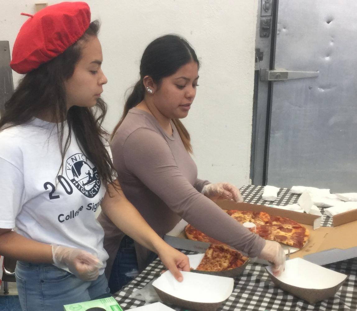 Venice High ASB students Tania Paz and Mona Viera serve pizza during the luncheon.