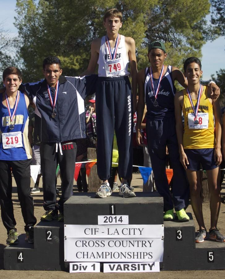 Junior, Paul Luevano, receiving medal after racing City Finals and achieving first place.