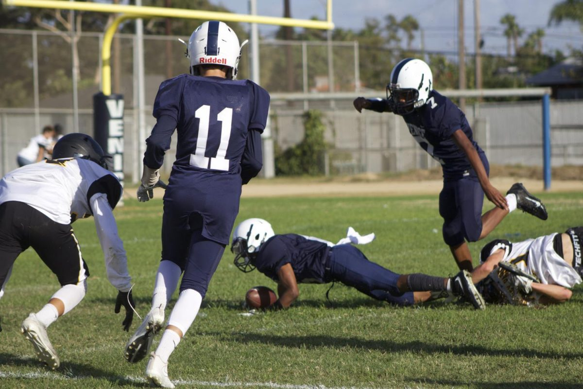 Venice JV football player, Lionel gets tackled by Newbury player.