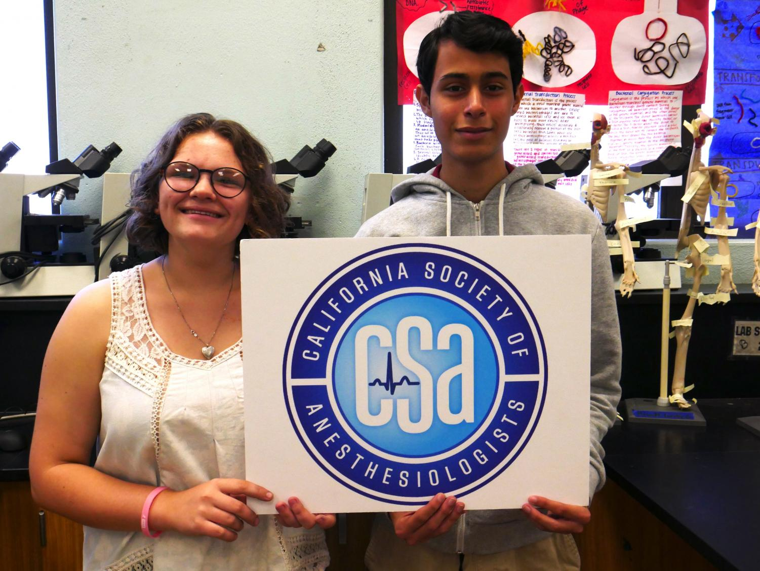STEMM Biomed students Camryn Butze and Alejandro Gonzalez pose with the CSA logo