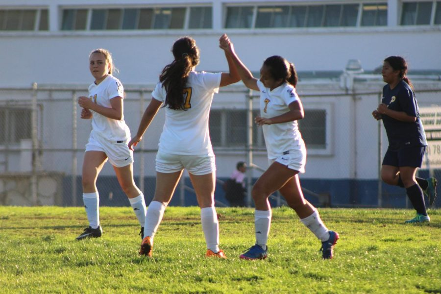 Victoria Corpuz (Number 7) high-fiving Gaby (Number 17) after a goal is scored.