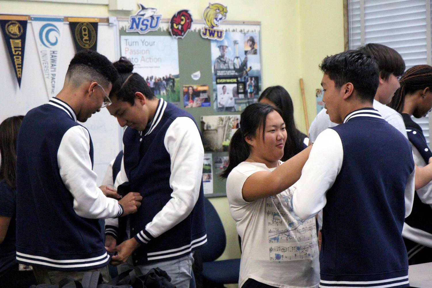 Jacket of Excellence recipients try on their jackets to make sure that they fit.