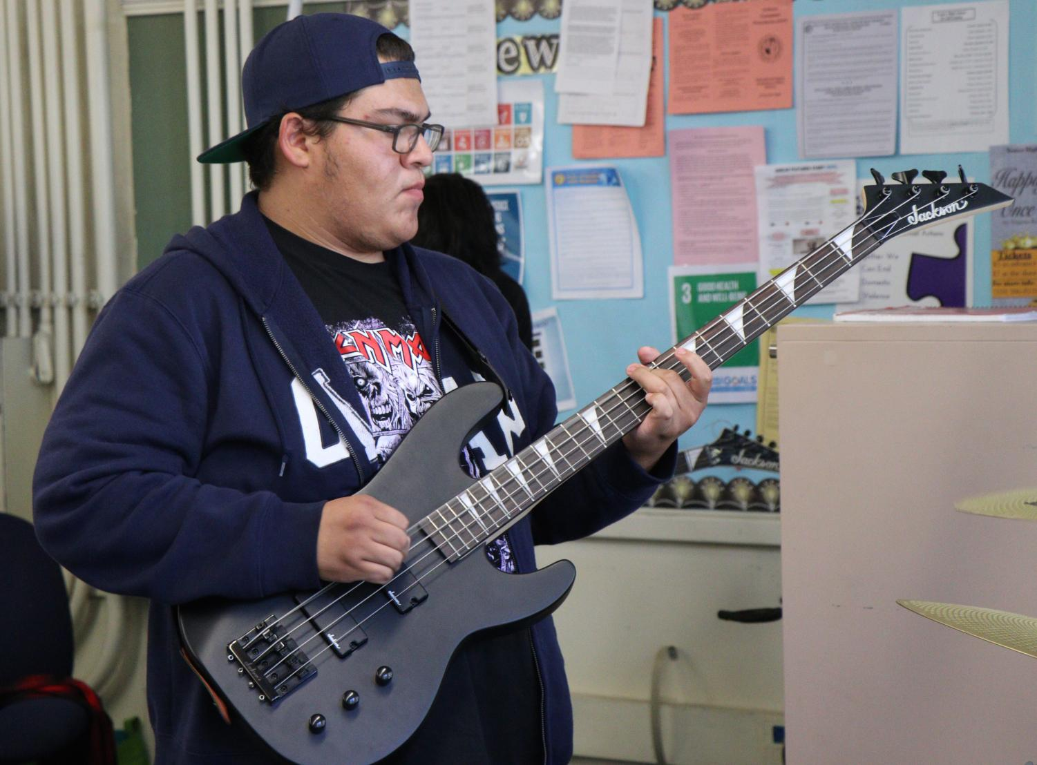 Bassist plays during Rock Band Club practice.