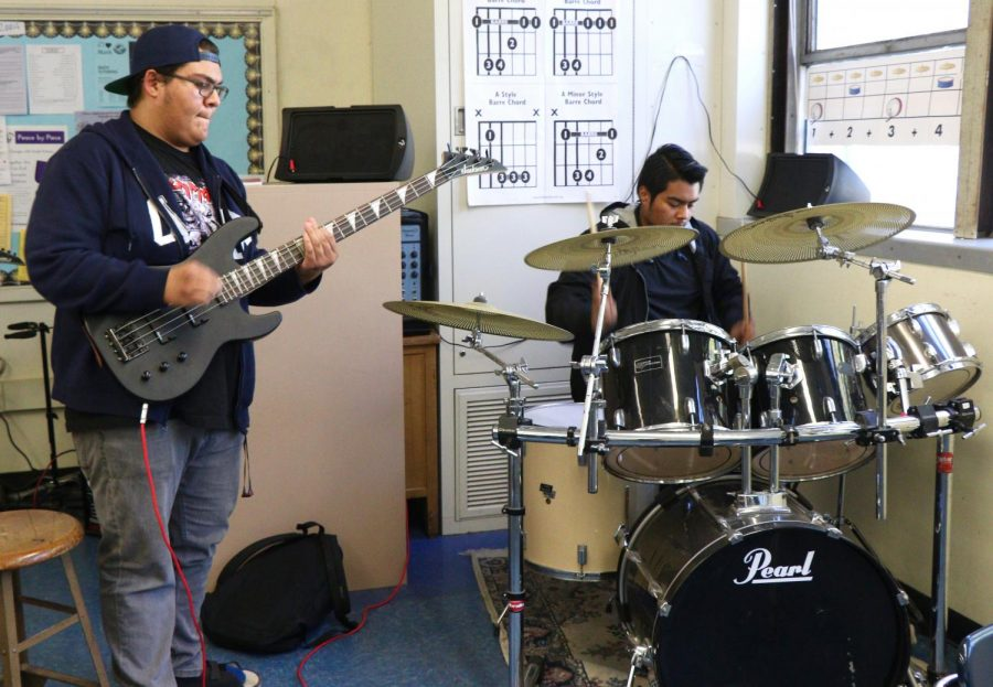 Drummer and guitarist play during Rock Band Club practice.