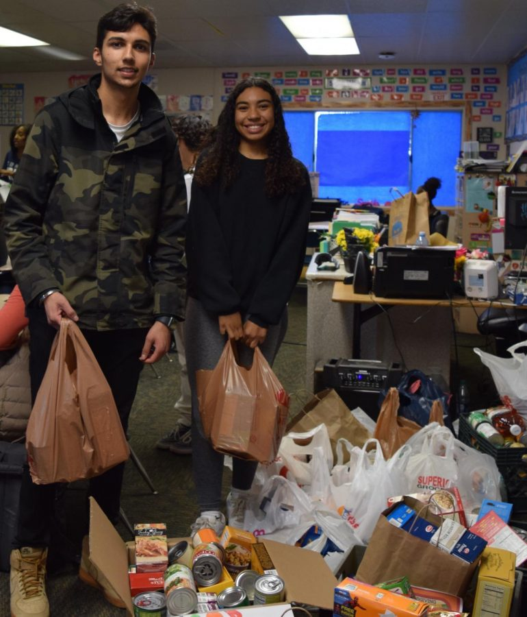 Aaliyah Nelson and Prabnoor Singh help distribute cans that were collected in this years Food Drive.