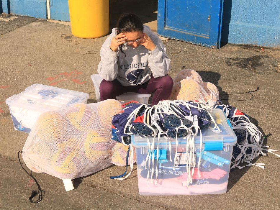 Ms. Sabbah, swim and waterpolo coach, surrounded by wet equipment.