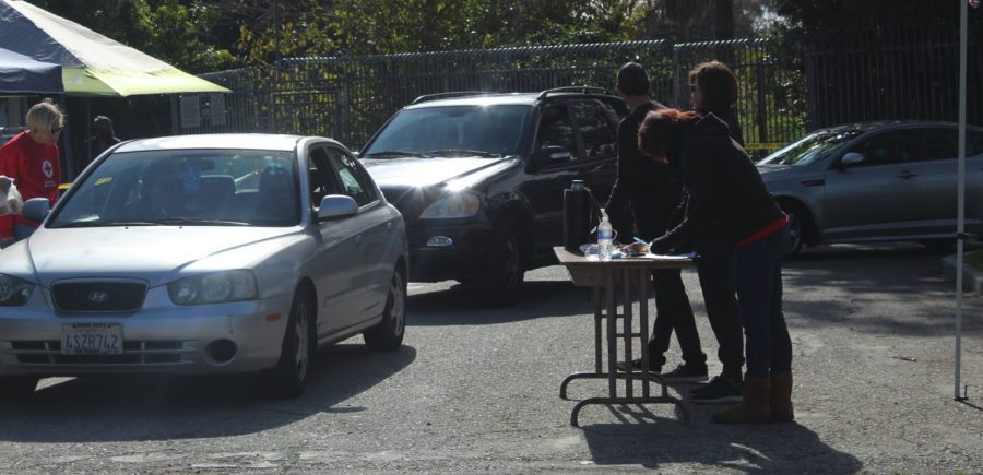A line of cars drives in as they are handed meals in their cars.