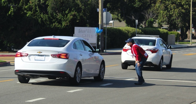 Red-Cross Volunteer telling a parent where to enter the Grab & Go location at Marina Del Rey Middle School.